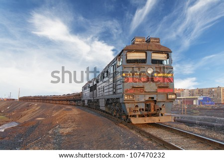 Front view of a locomotive with wagons hitched, illuminated by the setting sun.