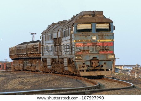 Front view of a locomotive with wagons hitched, illuminated by the setting sun. Railway track goes left. Horizontal shot.