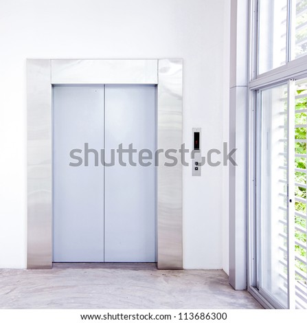 Front view of a modern elevator with closed doors in lobby
