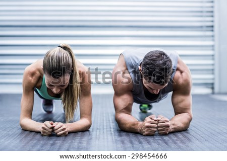 Front view of a muscular couple doing planking exercises #298454666