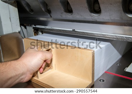 Front view of a paper guillotine used in commercial printing industry. Industrial knife cutter. Man\'s hand pushes the paper with special paper pusher
