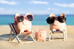 Front View Of A Pink Piggybank Family With Sunglasses On Sand At Beach