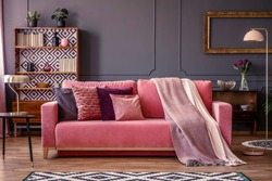 Front view of a pink sofa with pillows and blanket, vintage cupboard in the background in a glamorous living room interior