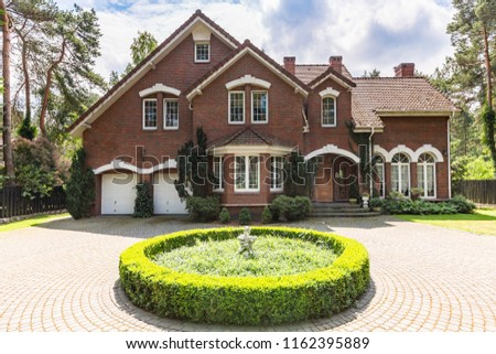 Front view of a red brick English style classic house with a steep roof, large windows and a circular driveway with a flowerbed decoration in the front.