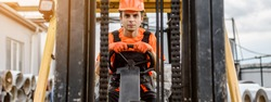 Front view of a serious face young caucasian man builder in overalls and orange protective helmet drive a construction loader machine on the construction materials store