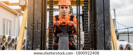 Front view of a serious face young caucasian man builder in overalls and orange protective helmet drive a construction loader machine on the construction materials store ストックフォト ©