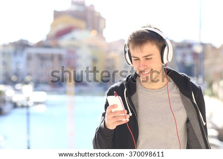 Front view of a teenager walking towards camera listening music with headphones from smart phone in a vacations destination