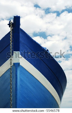 Front view of a wooden white and blue row fisherman boat under a cloudy sky #5546578
