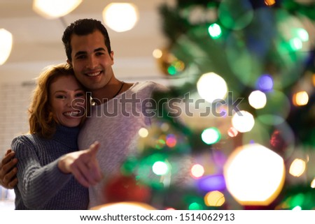 Front view of a young mixed race man and a young Caucasian woman smiling and embracing beside a decorated Christmas tree at home, defocussed in the foreground, the woman pointing to it #1514062913