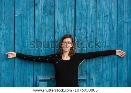 Front view of a young woman relaxing in introspection or meditation leaning on an old blue wooden door outside on a bright sunny spring day.