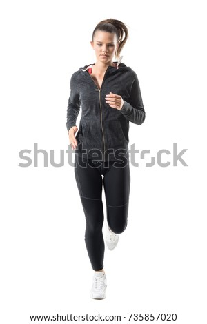 Front view of active healthy fit sporty woman running and looking down. Full body length portrait isolated on white background.