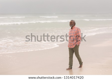 Front view of active senior man with hands in pocket walking on the beach