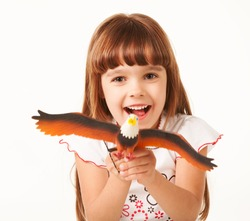 Front view of adorable joyful child holding bald eagle toy figure. Cute little girl with brown hair looking at camera and smiling. Isolated on white studio background. Concept of childhood and joy.