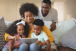 Front view of African American mother with her children using digital tablet on sofa while father looking at them. Social distancing and self isolation in quarantine lockdown for Coronavirus Covid19