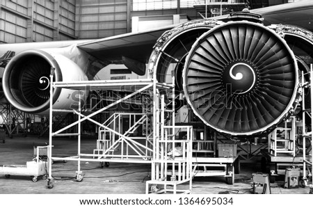 Front view of aircraft(airplane) engine during lift up from the floor by aircraft jack for maintenance .Aircraft on jack in hangar for maintenance service check by mechanic.