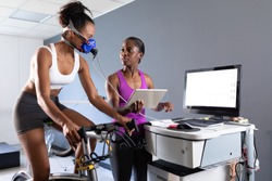 Front view of an African-American athletic woman doing a fitness test using a mask connected to a monitor while riding an exercise bike and an African-American woman monitoring her inside a room at a