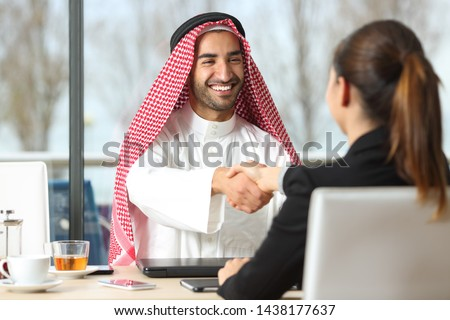 Front view of an arab businessman and marketer handshaking in a coffee shop or hotel bar