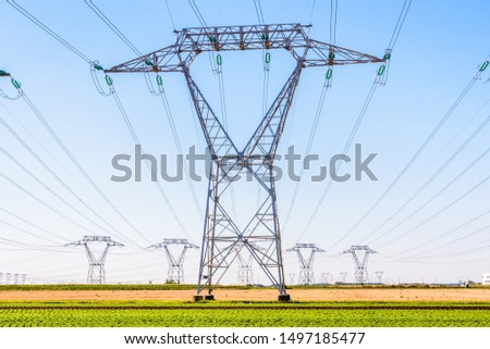 Front view of an electricity pylon in the french countryside with dozens of other pylons in the distance under a clear blue sky. #1497185477
