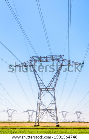 Front view of an electricity pylon in the french countryside with dozens of other pylons in the distance under a clear blue sky. #1501564748