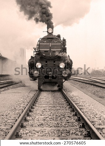 Front view of an old-fashioned steam locomotive in an austrian railway station. Scan from a  B&W negative.