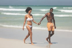 Front view of attractive multi ethnic couple walking hand in hand at beach on a sunny day