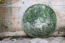 front view of big broken stone sculpture coin on brick cement wall