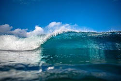 Front view of Big ocean wave in daylight. Blue sky with clouds. 