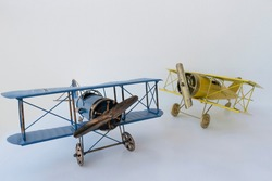 front view of blue and yellow metallic biplane retro airplane on white background