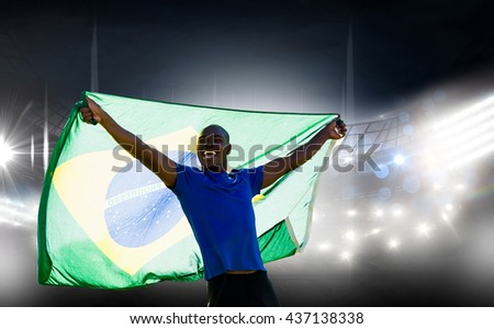 Front view of Brazilian sportsman is smiling and raising a flag against american football arena #437138338