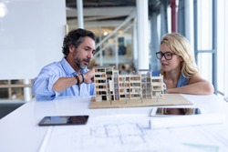 Front view of Caucasian male and female architect discussing over architectural model at table in a modern office. This is a casual creative start-up business office for a diverse team