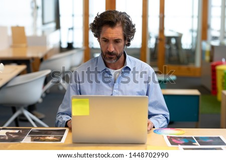 Front view of Caucasian male graphic designer using laptop at desk in office. This is a casual creative start-up business office for a diverse team
