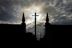 front view of cemetery in backlight, with gate, cross, stonework; towers and cloudy sky