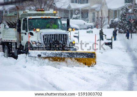 Front view of city services snow plow truck with yellow push blade clearing covered roads after heavy winter snow fall and passing by children bundled in warm clothes playing while flakes still fall. Foto stock ©