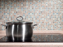 front view of closed used steel stockpot on black ceramic stove at home kitchen