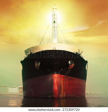 front view of commercial ship floating in port against sun light over sky