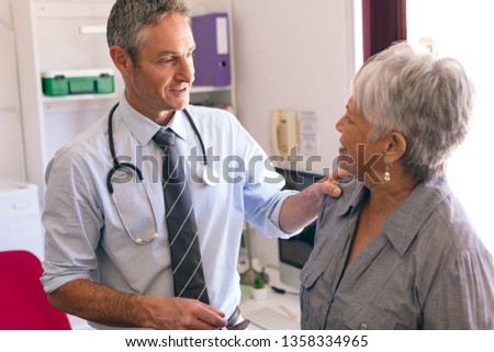 Front view of confident male doctor interacting with senior female patient in clinic at retirement home