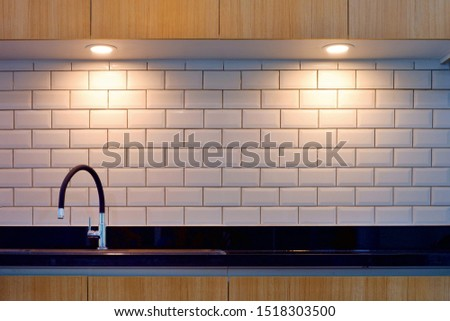 Front view of contemporary faucet and sink in black bar with lighting on white tiles wall surface and wooden countertops in modern kitchen style  #1518303500
