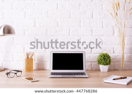 Front view of creative hipster desktop with blank laptop, smart phone, glasses, lamp, stationery and decorative items on white brick wall background. Mock up