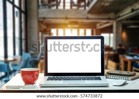 Front view of cup and laptop on table in office and background  in the coffee shop