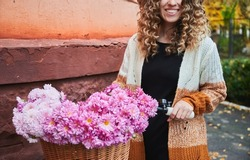 Front view of curly woman posing with bike near corner of brown building. Smiling female wearing brown cardigan is travelling by vintage cycle with big basket of pink camomiles. Concept of activity.