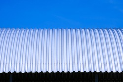 Front view of curved steel roof against blue clear sky background