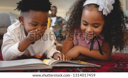 Front view of cute African American sibling lying on floor and reading a storybook in a comfortable home. Social distancing and self isolation in quarantine lockdown for Coronavirus Covid19