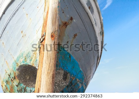 Front view of damaged with the time wooden fishing boat on Greek Kos island shore #292374863