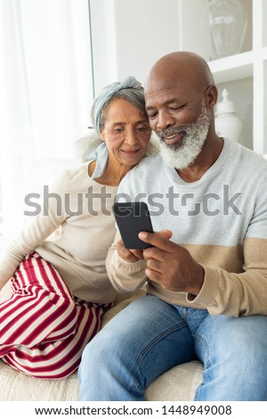 Front view of diverse couple using a smartphone on sofa. Authentic Senior Retired Life Concept