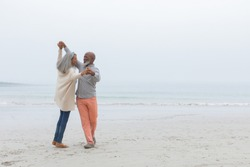 Front view of diverse happy senior couple smiling and dancing on the beach on cloudy day. Authentic Senior Retired Life Concept