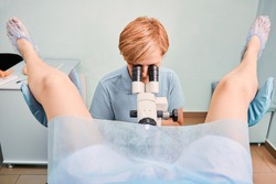 Front view of doctor in blue shirt examining woman with colposcope in gynecological clinic. Female patient laying in gynecological chair while gynecologist doing colposcopy examination.