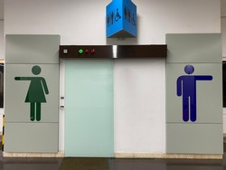 Front view of female and male restroom sign with the male, female and disable sign at the top. Public restroom at the airport. Toilet sign or symbol for male and female.
