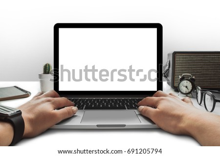 Front view of female hands working on laptop with blank white screen standing on the white office desk. Mock up, copy space for your text.