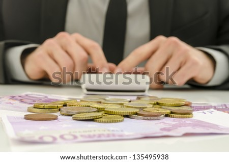 Front view of financial adviser working. With Euro banknotes and coins on his desk. Focus on money.