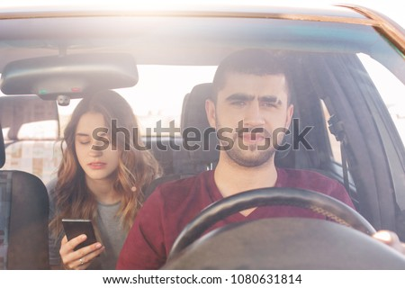 Front view of focused male driver sits at wheel and drives car while his girlfriend sits on back seat, holds smart phone and messages with friends or finds way in online map. Enjoy travel together